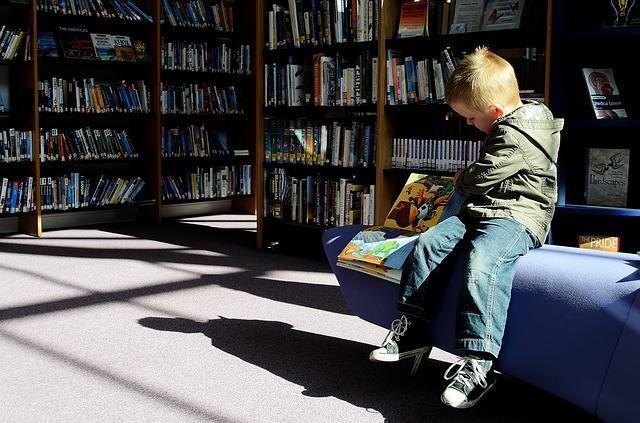 Czytające dziecko w bibliotece