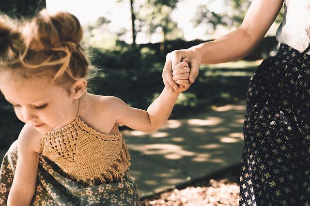 Matka prowadzi córkę za rękę