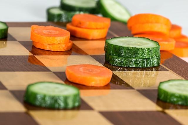 Plasterki ogórka i marchewki na szachownicy